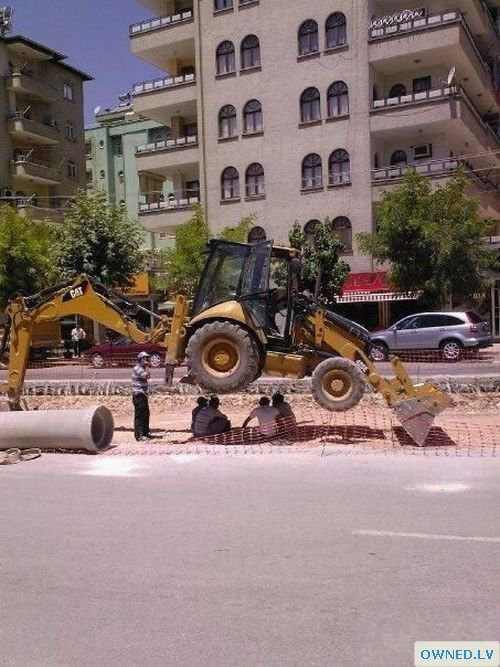 Construction workers under a bobcat lol
